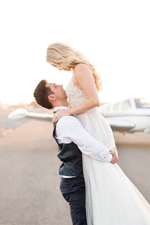 Orange-county-wedding-at-fullerton-hangers-bride-and-groom-carrying-bride