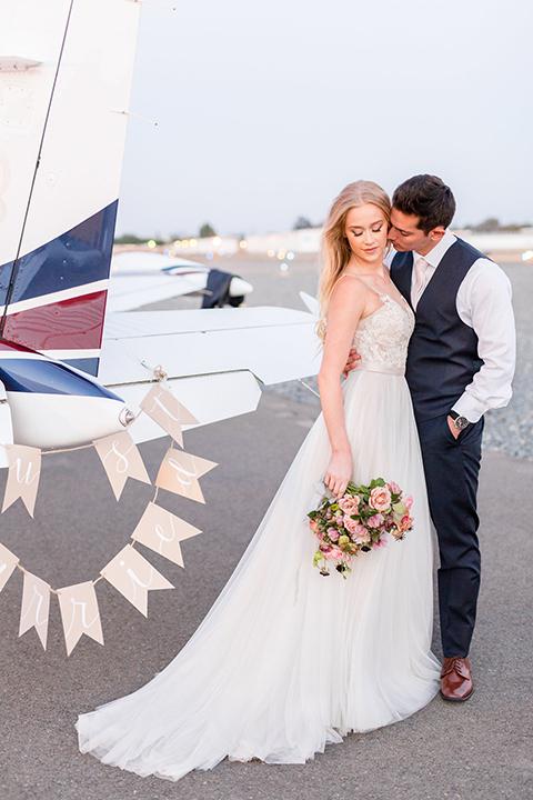 Orange-county-wedding-at-fullerton-hangers-bride-and-groom-standing-by-plane-hugging