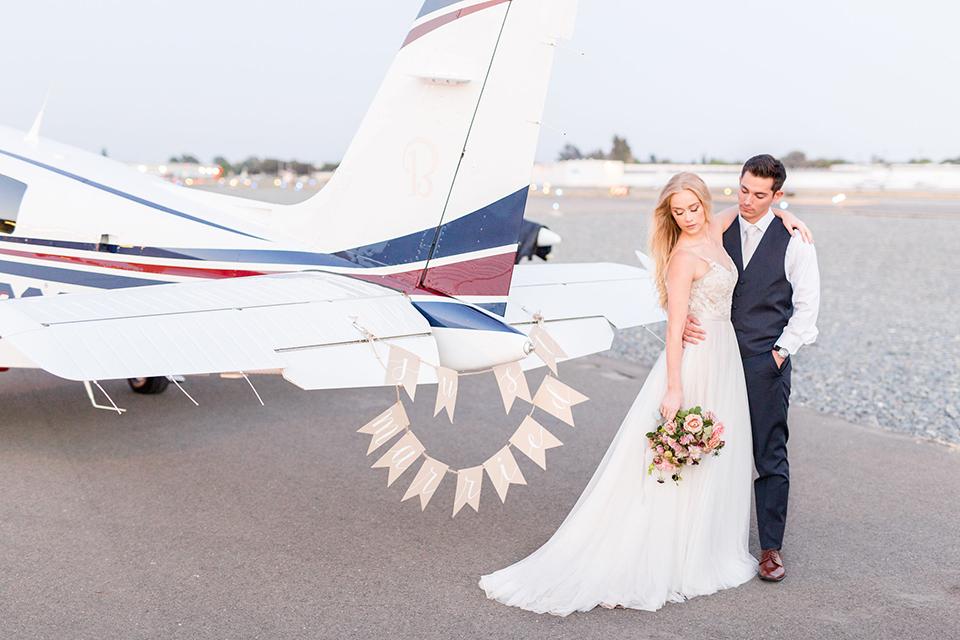 Orange-county-wedding-at-fullerton-hangers-bride-and-groom-standing-by-plane