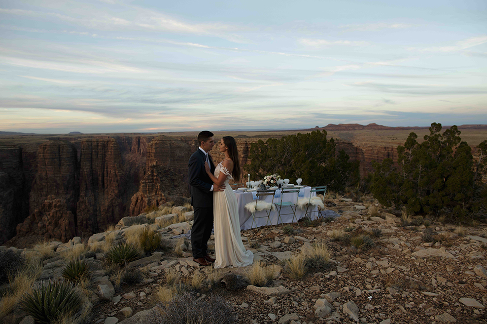 Grand-canyon-wedding-shoot-bride-and-groom-next-to-table-hugging