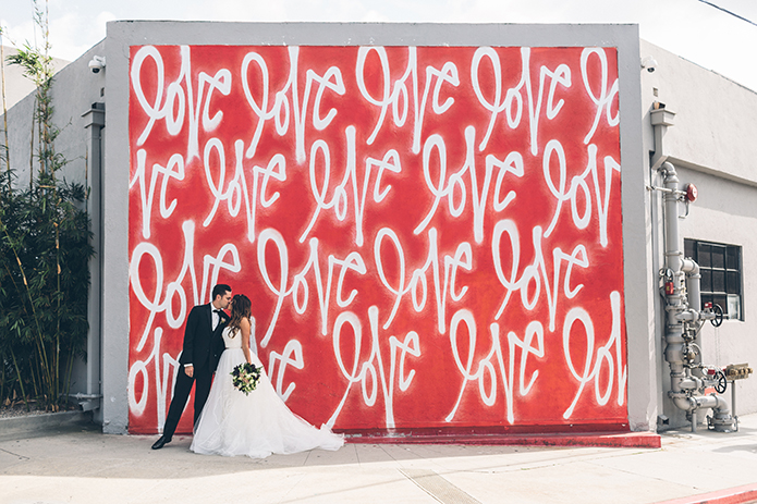 outdoor-boho-rustic-wedding-bride-and-groom-kissing-in-front-of-orange-love-wall