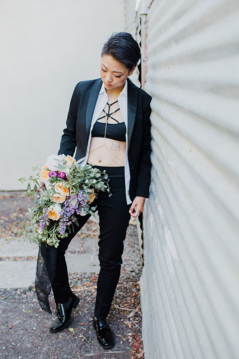 Los angeles same sex wedding shoot bride black womens tuxedo holding floral bouquet