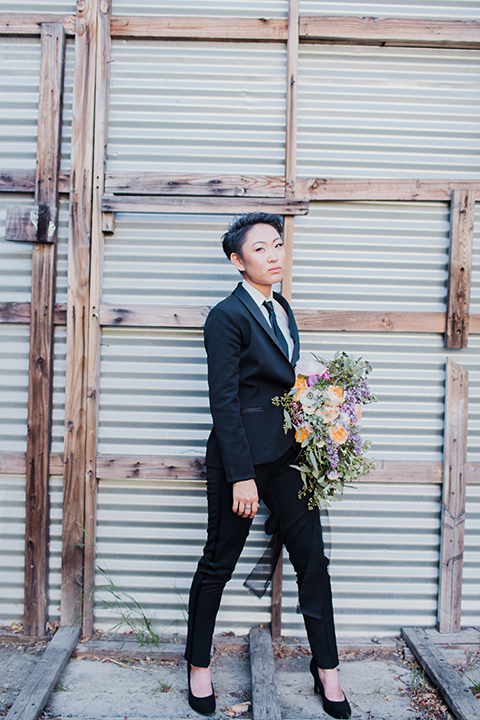 Los angeles same sex wedding shoot bride black womens tuxedo with tie holding flowers