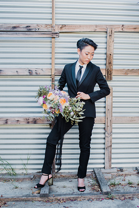 Los angeles same sex wedding shoot bride black womens tuxedo with tie holding jacket
