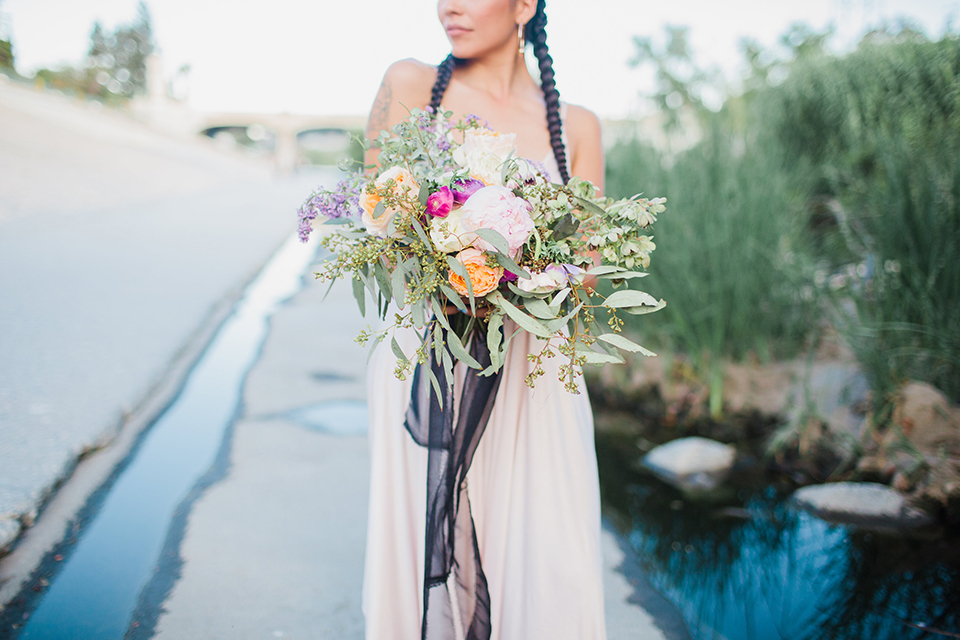 Los angeles same sex wedding shoot bride white dress holding floral bouquet