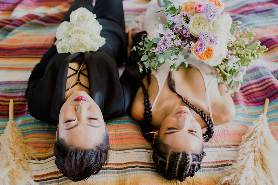 Los angeles same sex wedding shoot brides laying down with flowers