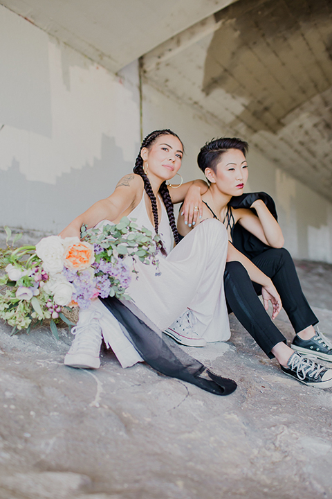 Los angeles same sex wedding shoot brides sitting with floral bouquet