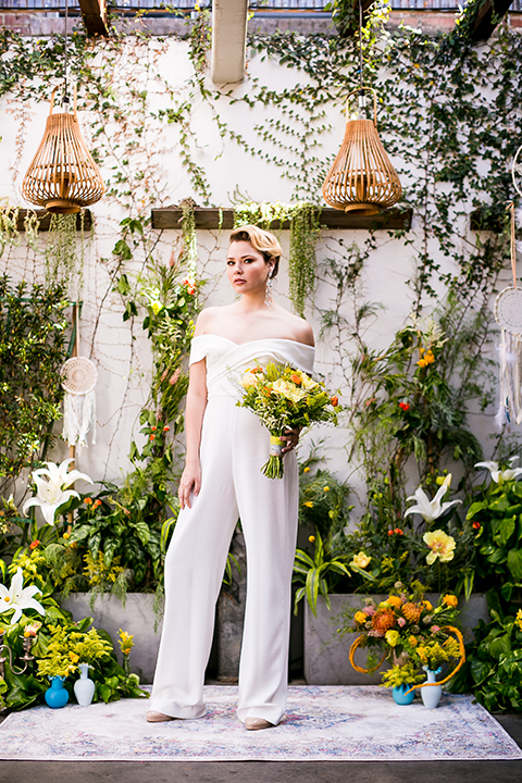 Lesbian-wedding-shoot-at-madera-kitchen-bride-white-jumpsuit-holding-bouquet
