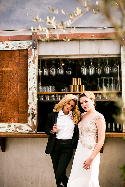 Lesbian-wedding-shoot-at-madera-kitchen-brides-hugging-standing