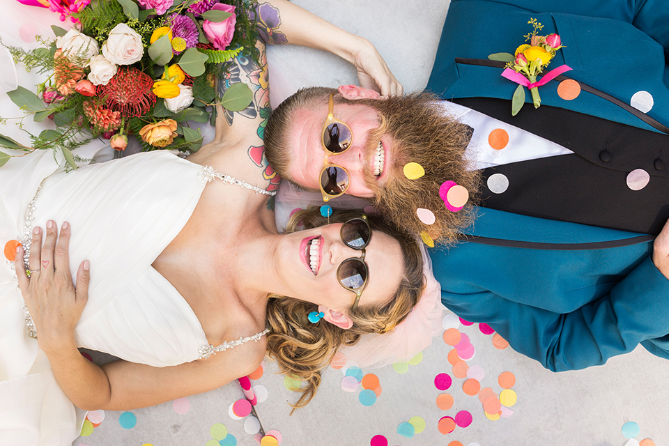 Long-beach-wedding-shoot-at-howl-bride-and-groom-laying-down-with-confetti