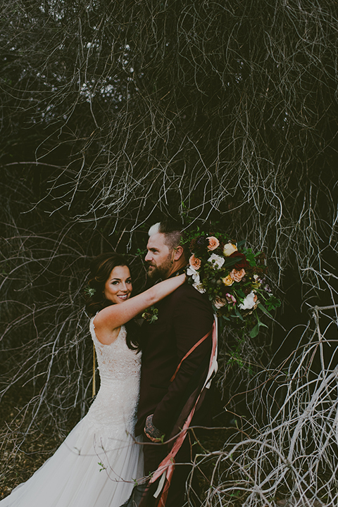 San-diego-outdoor-wedding-shoot-at-viejas-casino-and-resort-bride-and-groom-hugging-holding-floral-bridal-bouquet