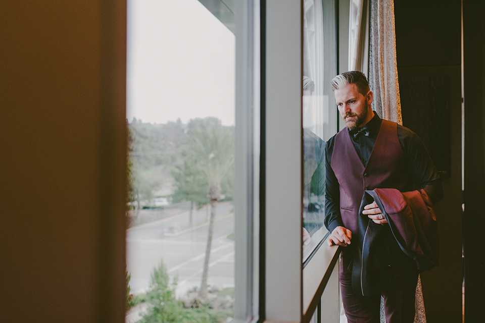 San-diego-outdoor-wedding-shoot-at-viejas-casino-and-resort-groom-burgundy-tuxedo-standing-by-window