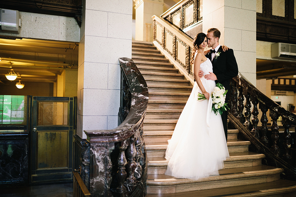 Los-angeles-wedding-at-the-majestic-bride-and-groom-standing-on-stairs-hugging-smiling