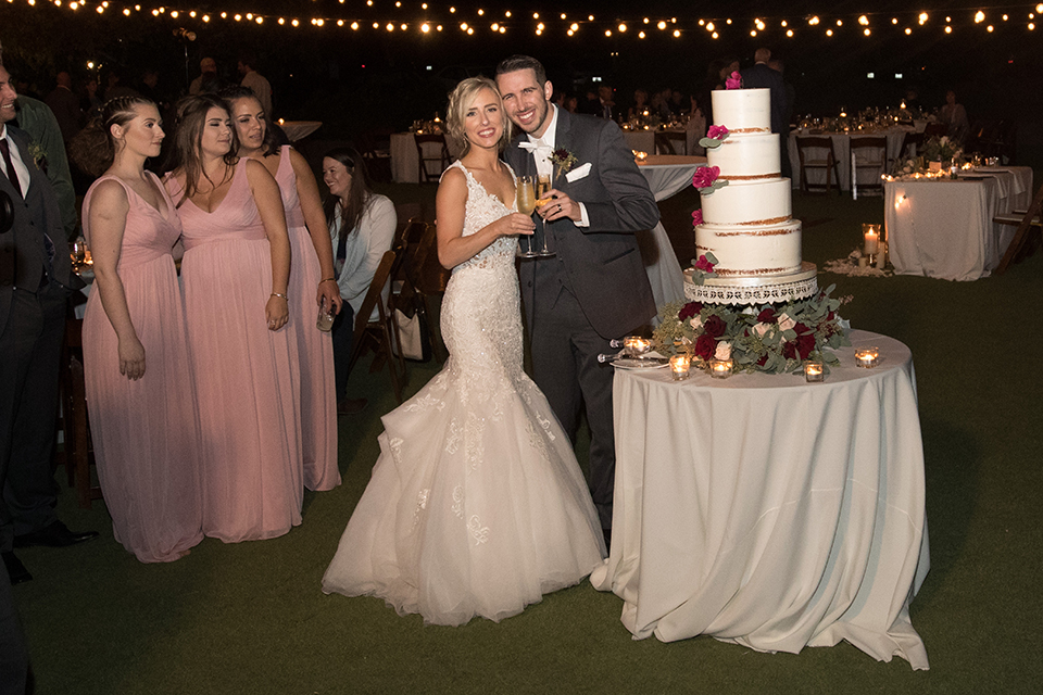 Orange-county-wedding-at-the-hamilton-oaks-winery-reception-bride-and-groom-cutting-cake-holding-drinks