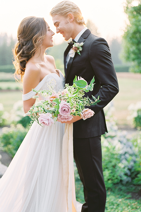 French-inspired-vineyard-wedding-bride-and-groom-hugging-and-holding-bouquet