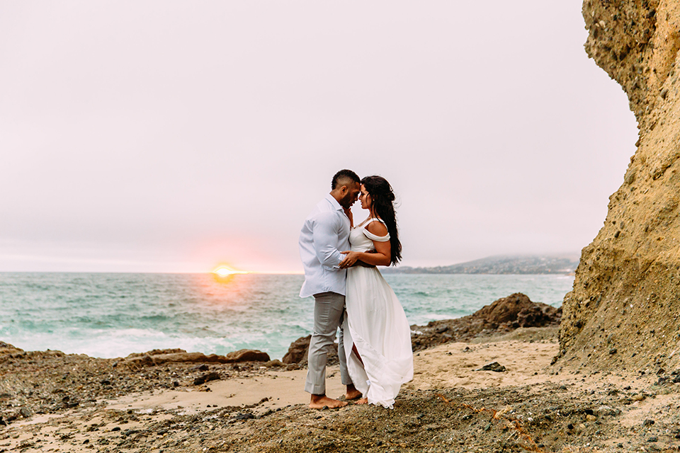 Orange-county-beach-wedding-in-dana-point-bride-and-groom-standing-and-hugging-at-sunset