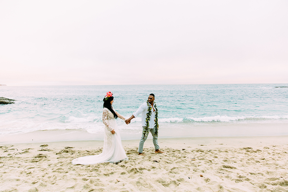 Orange-county-beach-wedding-in-dana-point-bride-and-groom-standing-holding-hands-walking