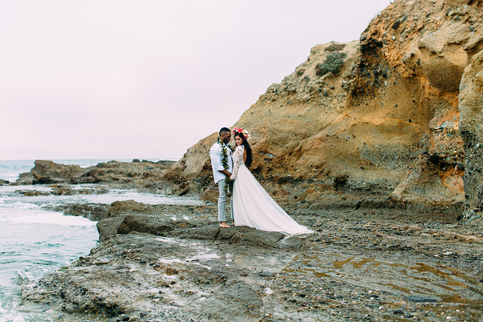 Orange-county-beach-wedding-in-dana-point-bride-and-groom-standing-on-rocks-hugging
