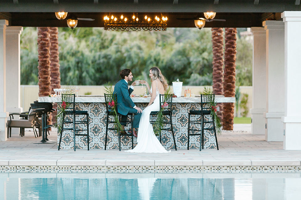 Palm-springs-wedding-shoot-at-old-polo-estate-bride-and-groom-sitting-holding-drinks