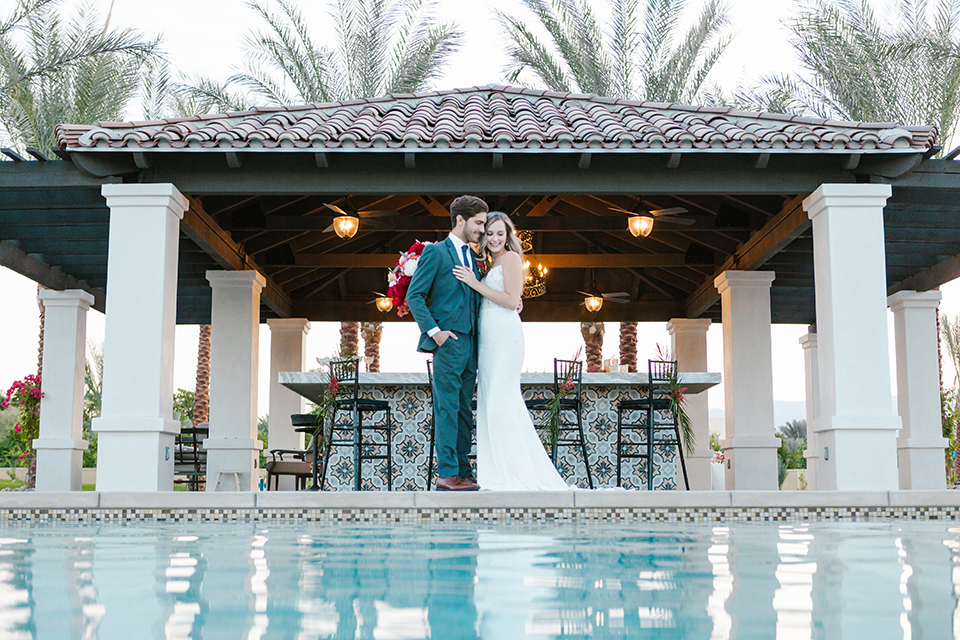 Palm-springs-wedding-shoot-at-old-polo-estate-bride-and-groom-standing-by-bar-smiling