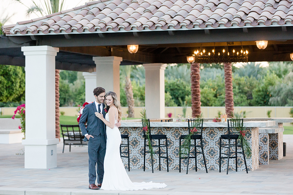 Palm-springs-wedding-shoot-at-old-polo-estate-bride-and-groom-standing-by-bar
