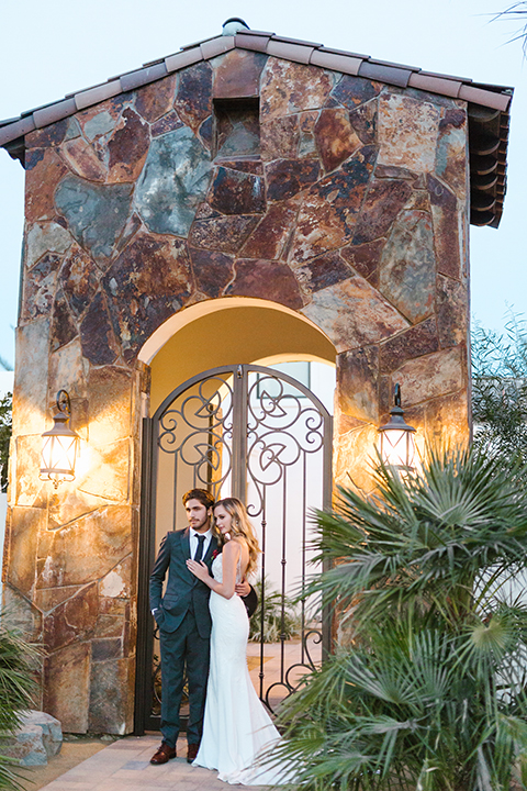 Palm-springs-wedding-shoot-at-old-polo-estate-bride-and-groom-standing-smiling-far-away
