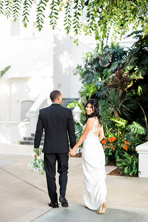 Park-hyatt-aviara-wedding-shoot-bride-and-groom-standing-holding-hands-smiling
