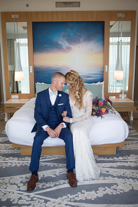 Orange-county-wedding-shoot-at-pasea-hotel-bride-and-groom-blue-suit-sitting-on-bed