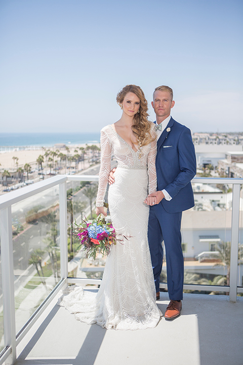 Orange-county-wedding-shoot-at-pasea-hotel-bride-and-groom-blue-suit-standing-on-balcony-holding-floral-bouquet