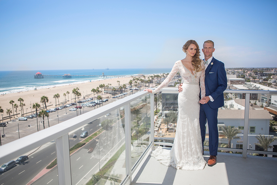 Orange-county-wedding-shoot-at-pasea-hotel-bride-and-groom-blue-suit-standing-on-balcony