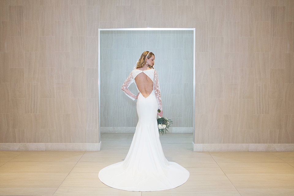 Orange-county-wedding-shoot-at-pasea-hotel-bride-lace-gown-with-sleeves-and-open-back-design-holding-bouquet