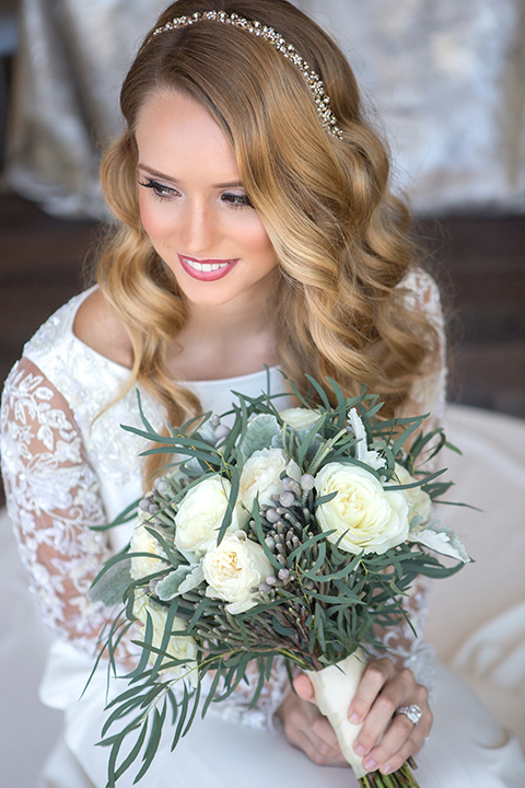 Orange-county-wedding-shoot-at-pasea-hotel-bride-lace-gown-with-sleeves-holding-floral-bouquet-close-up