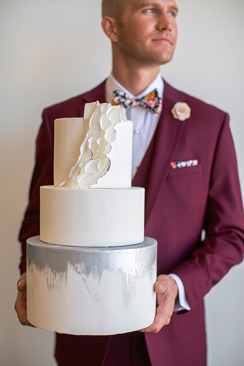 Orange-county-wedding-shoot-at-pasea-hotel-groom-burgundy-suit-with-a-floral-bow-tie-holding-cake
