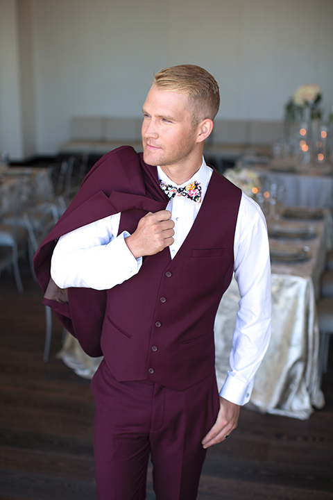 Orange-county-wedding-shoot-at-pasea-hotel-groom-burgundy-suit-with-a-floral-bow-tie-holding-jacket