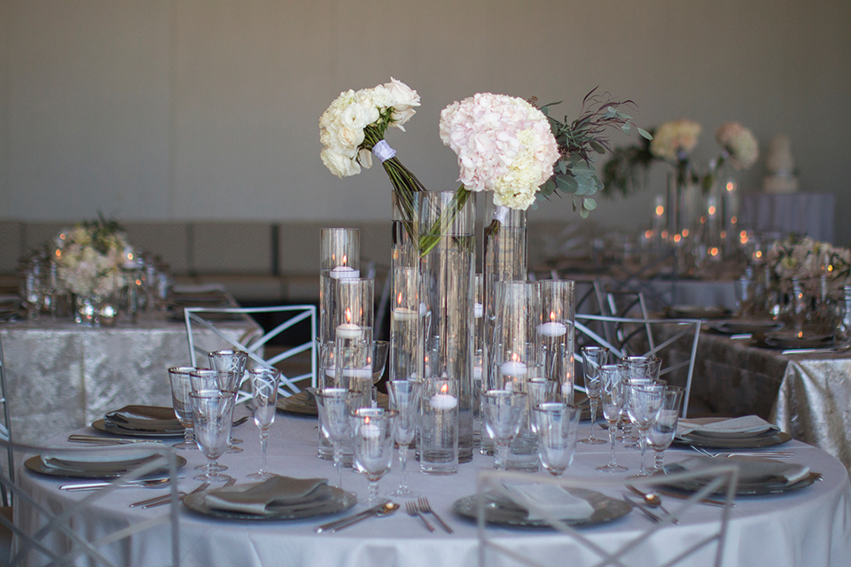 Orange-county-wedding-shoot-at-pasea-hotel-table-set-up-with-silver-table-linen-and-place-settings-with-flowers-and-floating-candles