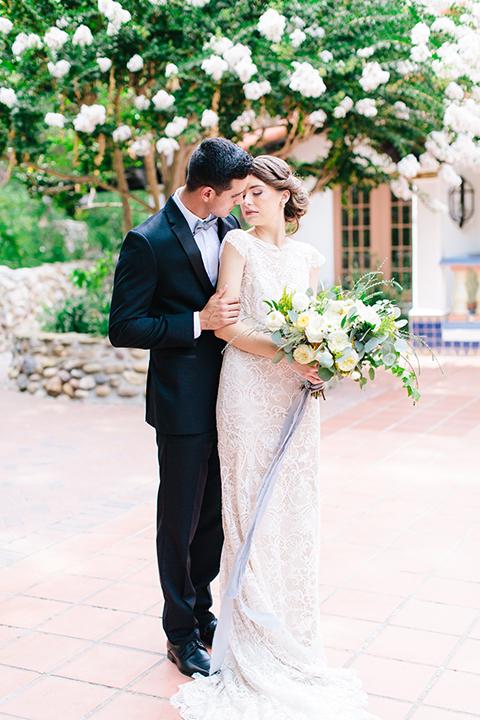 Rancho-las-lomas-outdoor-wedding-bride-and-groom-hugging-holding-bouquet