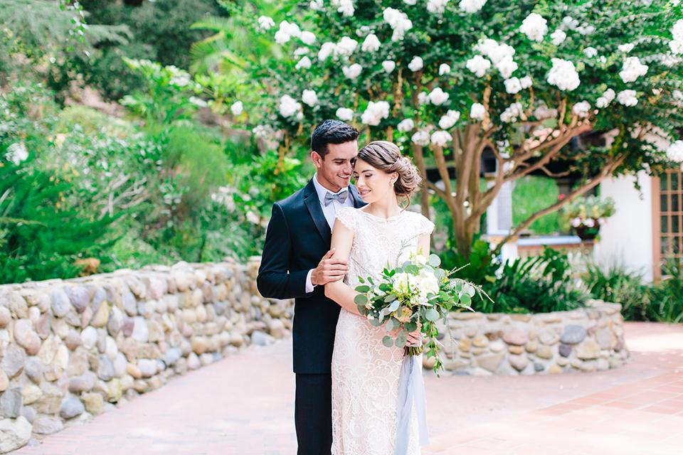 Rancho-las-lomas-outdoor-wedding-bride-and-groom-hugging-with-bouquet