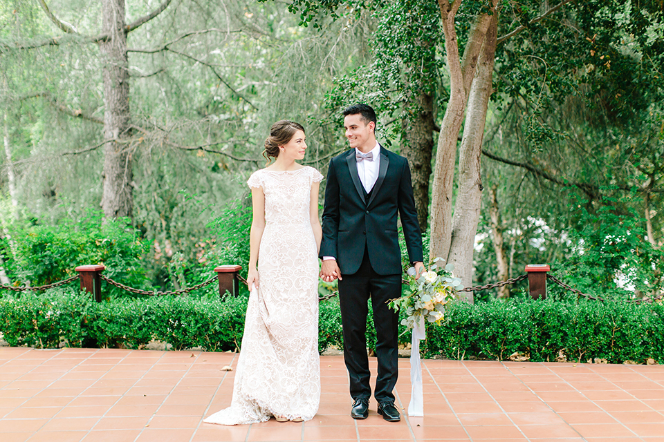 Rancho-las-lomas-outdoor-wedding-bride-and-groom-standing-holding-hands-and-bouquet