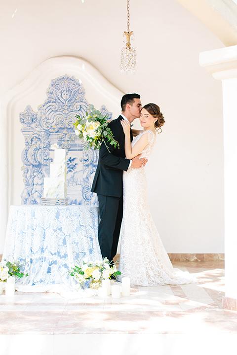 Rancho-las-lomas-outdoor-wedding-bride-and-groom-standing-hugging-by-cake
