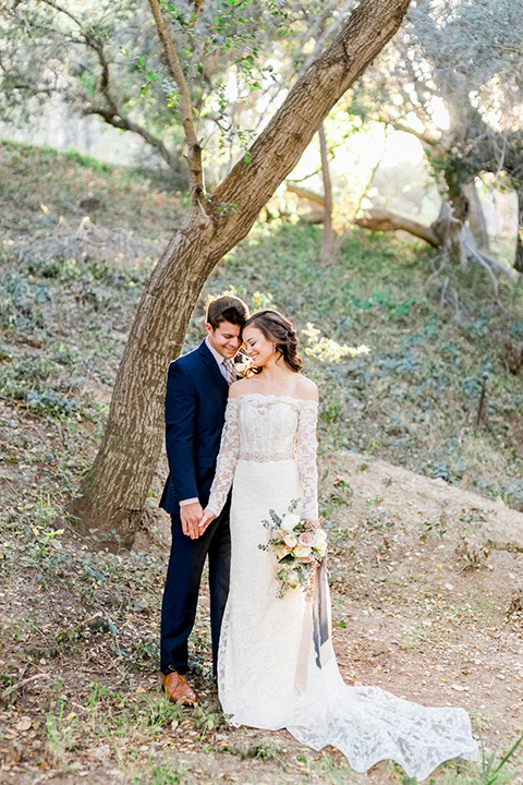 Rancho-las-lomas-outdoor-wedding-shoot-bride-and-groom-holding-hands-and-smiling