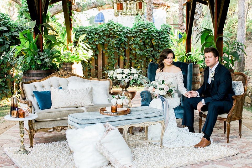 Rancho-las-lomas-outdoor-wedding-shoot-bride-and-groom-holding-hands-sitting-down-in-lounge-furniture