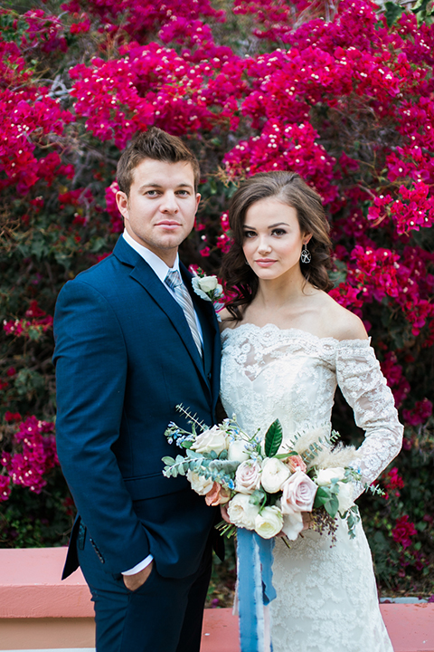 Rancho-las-lomas-outdoor-wedding-shoot-bride-and-groom-standing-in-front-of-pink-flowers