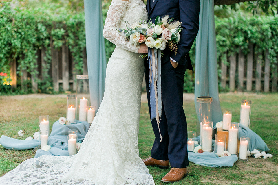 Rancho-las-lomas-outdoor-wedding-shoot-ceremony-bride-and-groom-standing-close-up-holding-floral-bouquet