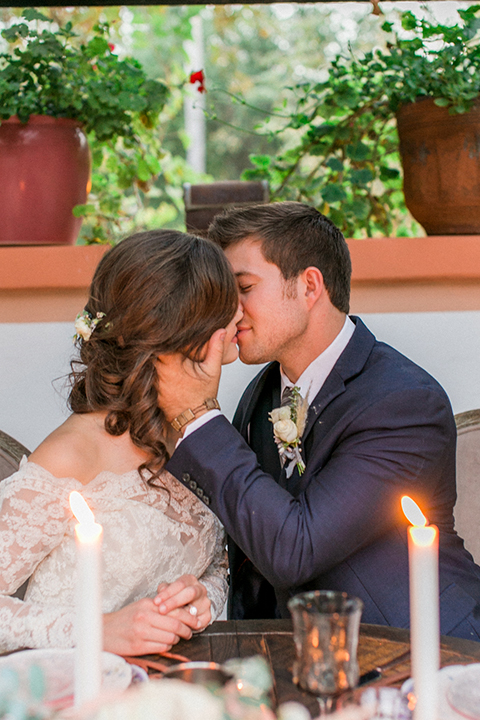 Rancho-las-lomas-outdoor-wedding-shoot-sweetheart-table-set-up-with-flower-and-candle-decor-bride-and-groom-kissing