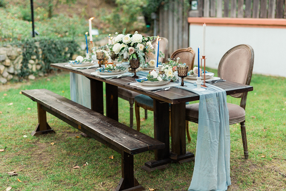 Rancho-las-lomas-outdoor-wedding-shoot-table-set-up-with-light-blue-table-runner-and-chairs-with-long-bench