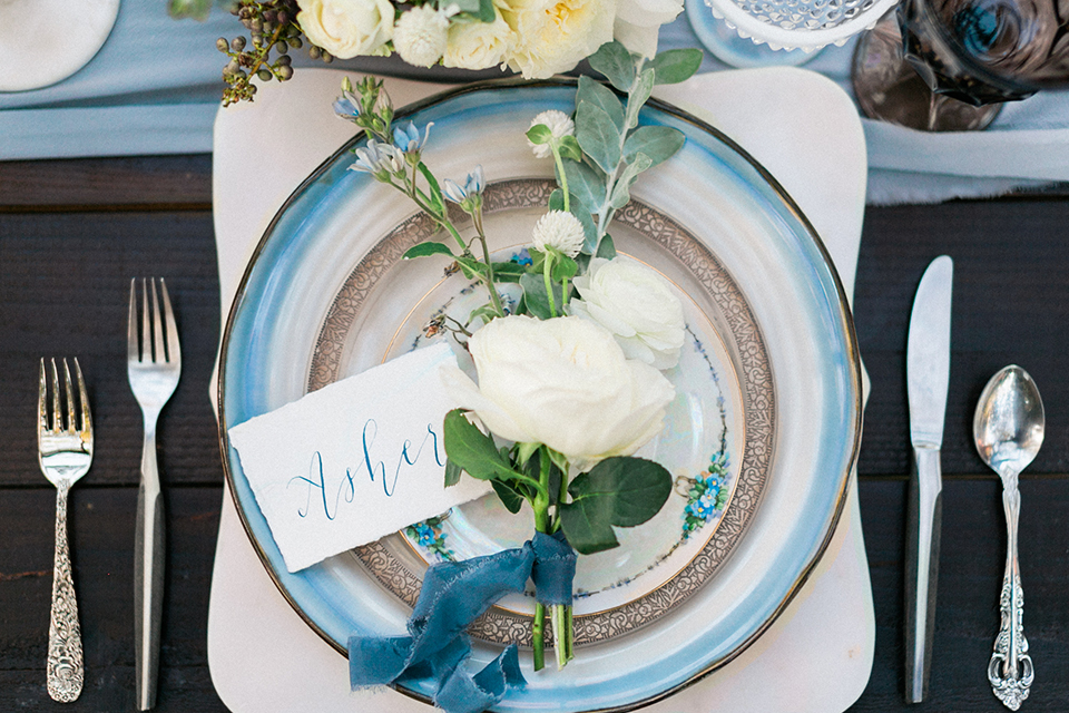 Rancho-las-lomas-outdoor-wedding-shoot-table-set-up-with-light-blue-table-runner-and-white-and-blue-place-setting