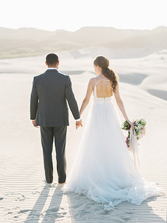 sand-dunes-wedding-shoot-back-of-bride-and-groom-holding-hands
