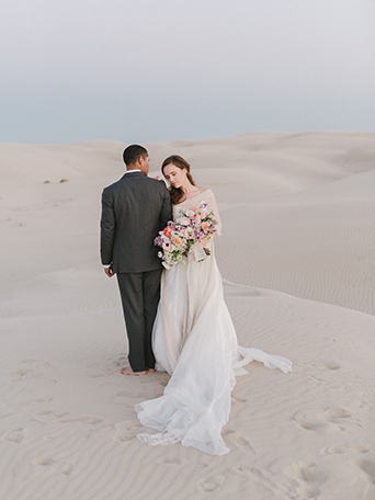 sand-dunes-wedding-shoot-back-of-groom-with-bride-holding-bouquet