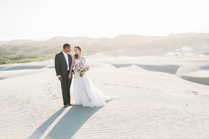 sand-dunes-wedding-shoot-bride-and-groom-far-away-holding-bouquet