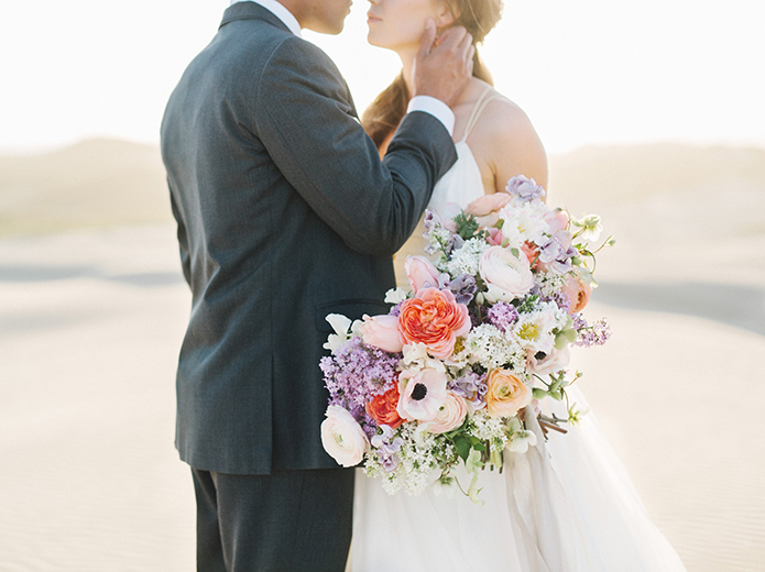 sand-dunes-wedding-shoot-bride-and-groom-holding-bouquet-close-up